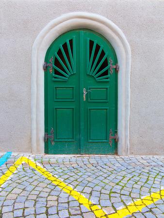 Rounded door on cobblestone street