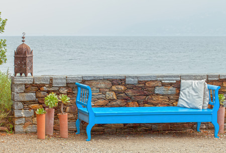 Blue bench next to wall on lake