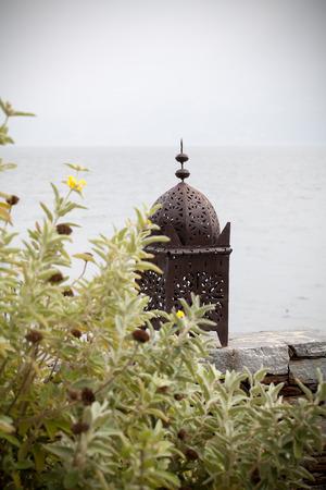 Moroccan lantern on stone ledge next to water Stok Fotoğraf