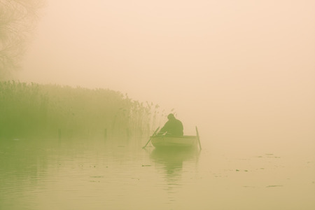 Fisherman prepares gear in rowboat on an early winter morning