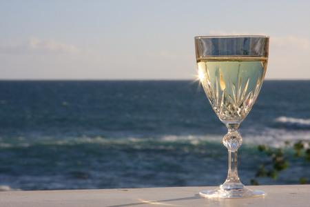 Sun rays shine through a solitary wine glass on the ocean Stok Fotoğraf