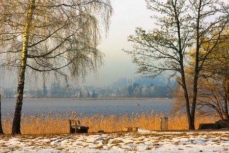 Multicolored winter scene with a boat on the lake