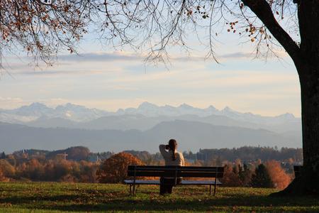 Woman on bench under a tree in autumn gazes towards alps Stok Fotoğraf - 33279105