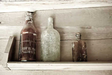 earth tone: Old bottles collecting dust on a barn shelf in Great Dixter, England. Stock Photo