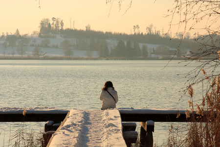 Lonely woman sitting on a pier in winter
