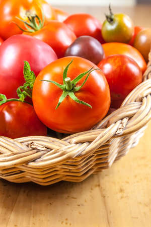 A bunch of tomatoes in a wicker basket on wooden table Stok Fotoğraf