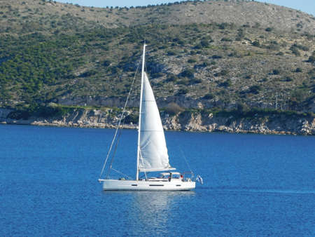 September 2020, Vouliagmeni, Attica, Greece. A white sailboat near the coast