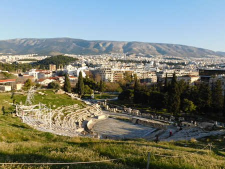 January 2019, Athens, Greece. View of the ancient theater of Dionysus, on the south slope of the Acropolis, and the city Imagens