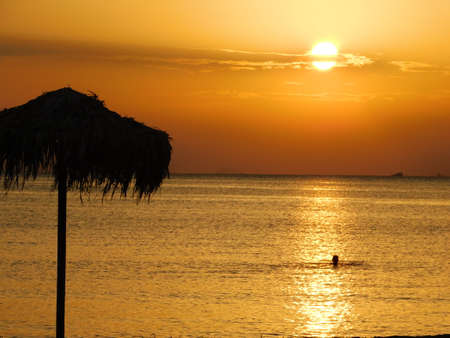 Man swimming in the golden sunset, near the shore of Glyfada, Greece