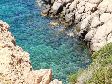 A rocky shore with emerald waters, in Attica, Greece