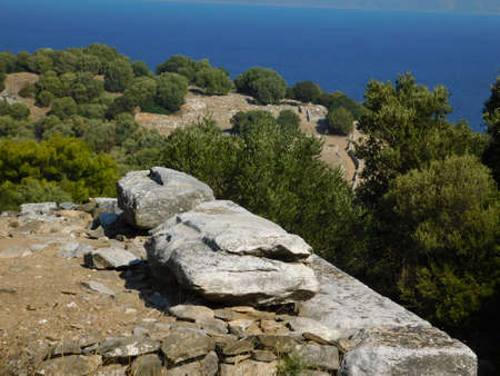 Ancient stones and a distant view of the ancient city of Rhamnous, in Attica, Greece Imagens