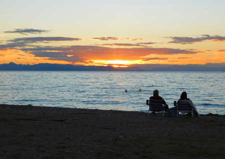 View of the sunset, and people on the beach of Glyfada, Greece