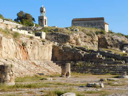 April 2018, Eleusis or Elefsina, Greece, View of the carved ancient worship ceremony building, the Telesterion, a small Christian church and a bell tower