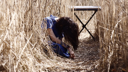 bass guitar women: Lonely girl and a synthesizer in cold reeds