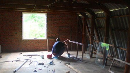 rafter: man making a frame in the attic, scattered items Stock Photo