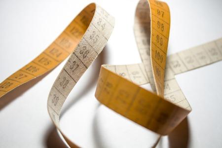measurement: Entangled measuring tape. Measuring meter orange color Stock Photo