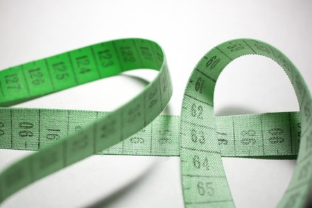 entangled: Entangled measuring tape. Measuring meter Green color Stock Photo