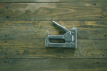 staple gun: staple gun on a wooden surface covered with impregnation