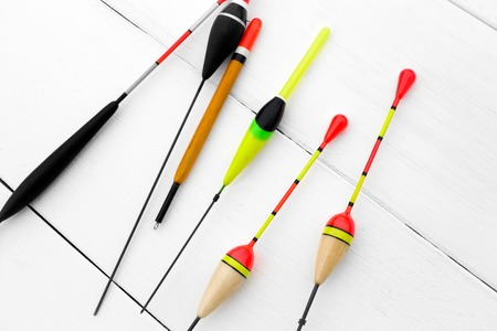 bobber: Six floats for fishing on a wooden surface, white background.