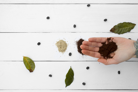 addictive drinking: Creative mind, Ground coffee on hand. Green leaves drying, types of coffee on a wooden table top white, black and white coffee beans Stock Photo