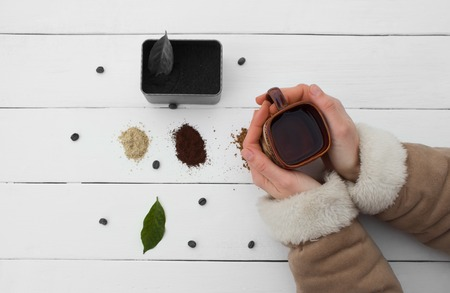 addictive drinking: Creative work with a cup of boiling water in his hands. A handful of coffee, green, ground and soluble coffee leaves on a wooden table top white, black and white coffee beans Bank