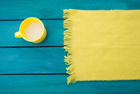 table surface: Mug of milk and a yellow scarf on a turquoise surface background wooden table