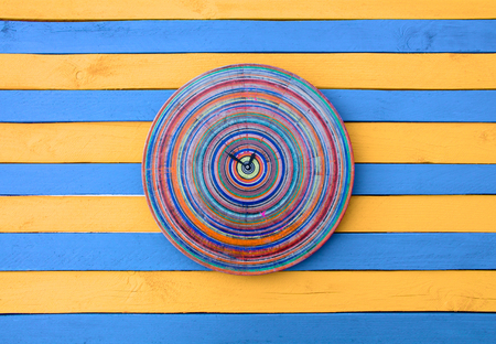 show time: Vintage creative clock blue and yellow striped wood texture surface. Bright colors show time