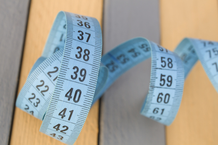 measurement: Entangled measuring tape. Measuring meter bluee color, gray and yellow stripes, the background Stock Photo