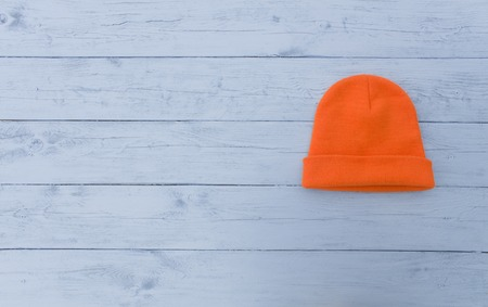 acrylic yarn: Fluorescent orange knit cap on a rough wooden surface light blue Stock Photo