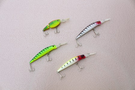 wobbler: Four wobbler for fishing on a scabrous surface, the background light beige Stock Photo