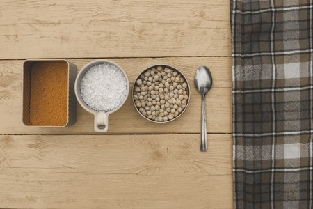 ques: Figure chickpeas and spices lie in different wooden utensils on a white background with a napkin in a cage Stock Photo