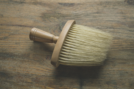 colouration: Large brush made of wood lying on a wooden table top close-up