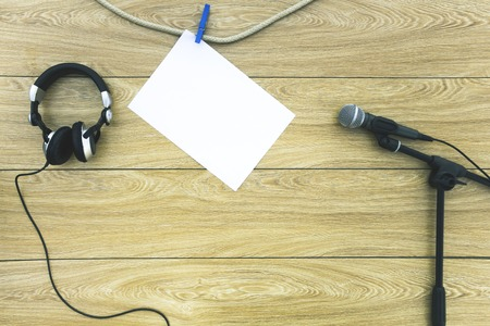 spoken: Microphone on the stand, headphones and a sheet of paper on a clothespin on a wooden background