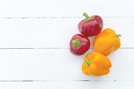 Four pepper paprika yellow and red on a white table