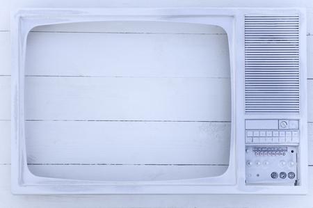 古いテレビは、白のアクリル塗料でコーティングされています。白い木製の背景。優秀なレトロ。創造的な内装。モダンなスタイルで保護されます