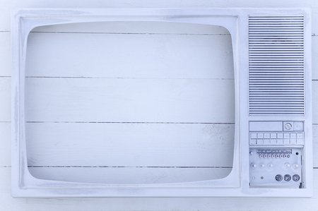 Old TV screen is coated with white acrylic paint. On a white wooden background. Excellent retro. Creative decor. Secured by modern style.
