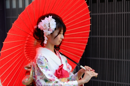 KYOTO,JAPAN - OCTOBER 14  Maiko poses for a photographer with red umbrella on October 14, 2013 in kyoto  Editorial