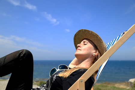 basque woman: Blonde woman on deck chair-France Stock Photo