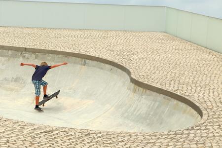 BIARRITZ, FRANCE - JULY 28, 2014: Skater boy trains his hobby in the skate park on July 28, in Biarritz-France.