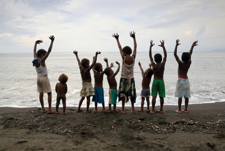 youngs: AMBRYM,VANUATU-OCTOBER 10, 2014: Eleven kids playing on the beach while their parents work in the village shop on October 10, in Olal-Vanuatu.