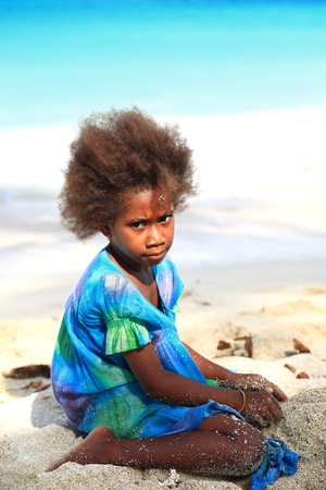 youngs: ESPIRITU SANTO,VANUATU-OCTOBER 19, 2014:  Ni-vanuatu girl shows the local fashion in hair cutting while playing on the beach on October 19, in Port Olry-Vanuatu.