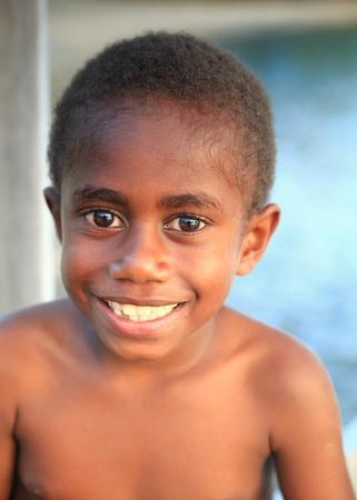 local business: PANGI,VANUATU-OCTOBER 14, 2014: Native boy takes care of her brother while their parents work in a local business on October 14, in Pentecostes-Vanuatu.