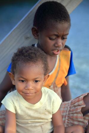 local business: PANGI,VANUATU-OCTOBER 14, 2014: Native boy takes care of his brother while their parents work in a local business on October 14, in Pentecostes-Vanuatu.