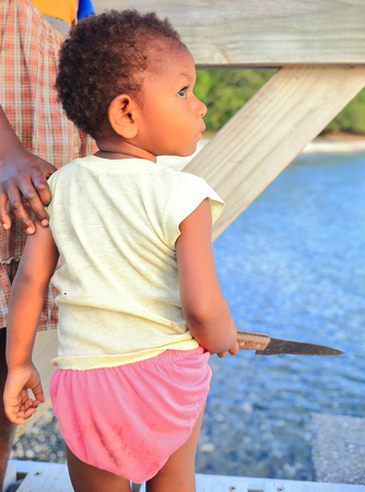 learns: PANGI,VANUATU-OCTOBER 14, 2014:Baby learns to handle the indispensable machete in everyday life in Vanuatu on October 14, in Pentecostes-Vanuatu. Editorial