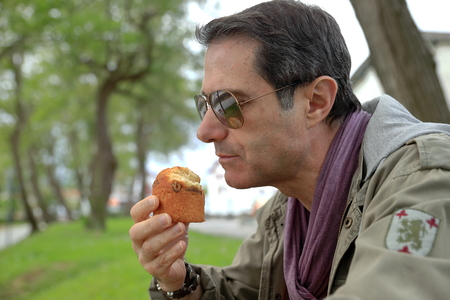 area sexy: Man eating a muffin Stock Photo
