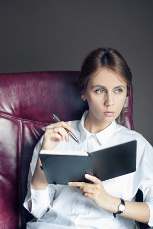 superintendent: Young business woman thinks about something sitting in a armchair