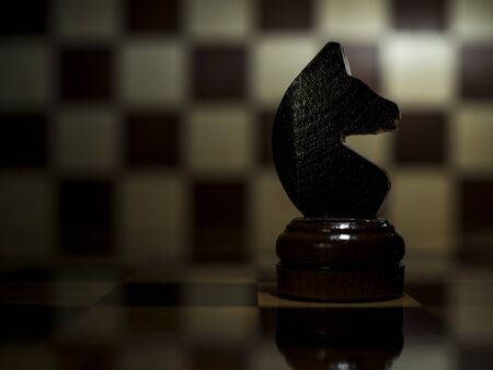 close-up of a lone black horse on a chessboard, still life