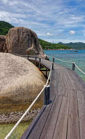 Ko Tao island National Park, wooden bridge and bigger boulder in the coastline sea view. Thailand country.