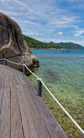 Ko Tao island National Park, wooden bridge and bigger boulder in the coastline sea view. Thailand country. Imagens