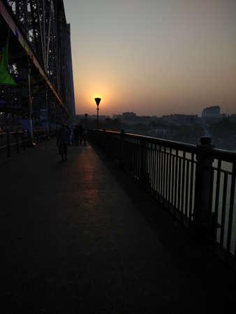 Sunrise at Howrah Bridge. Suns behind the street lamp